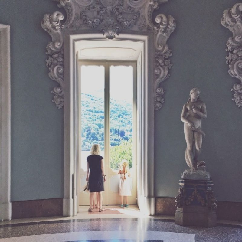 Window in old, luxurious palace with Greek statue, and green hill view